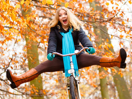 Fall active lifestyle concept. Happy crazy woman girl vivid color shawl relaxing in autumn park riding bicycle with her legs in the air having fun
