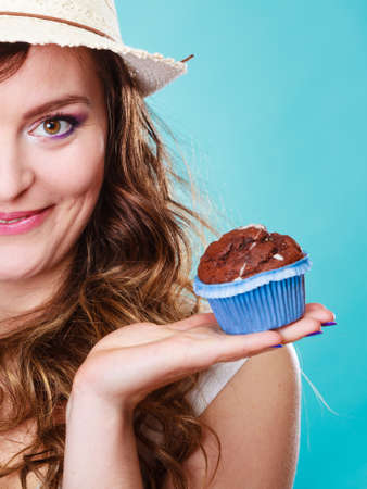 eating pastry: Bakery, sweet food and people concept. Closeup part of face smiling summer woman curly hair straw hat holding chocolate cake cupcake in hand blue background