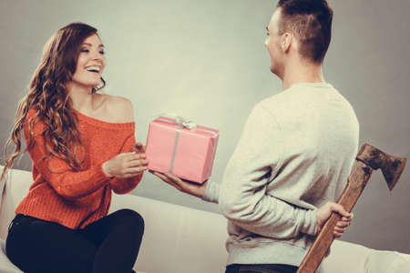 insincere: Sneaky insincere man holding axe giving gift present box to woman. Husband concealing hiding his true feelings from happy trusting wife. Untrue false intention. Relationship problems. Instagram.