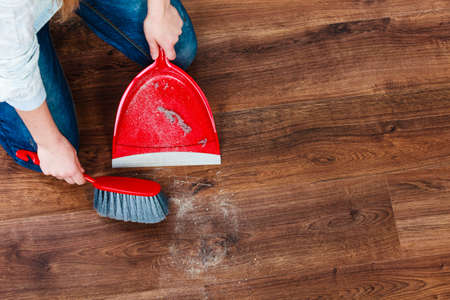 apartment cleaning: Cleanup housework concept. Closeup cleaning woman sweeping wooden floor with red small whisk broom and dustpan indoor Stock Photo