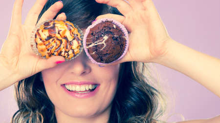 hands covering eyes: Bakery, sweet food and happiness concept. Closeup smiling woman having fun holding cakes in hands covering eyes with cupcakes pink background Stock Photo