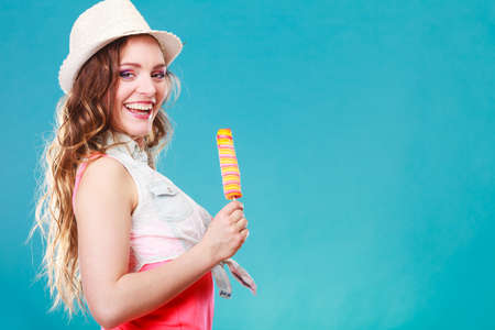 woman fashionable: Summer vacation happiness concept. Smiling joyful and cheerful woman fashionable female model eating popsicle ice pop on blue background