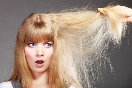 bad hair: Haircare. Blonde woman with her damaged dry hair angry face expression gray background