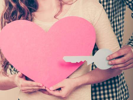 liebe: Paarholdingpapier Schlüssel zum Herzen Zeichen Liebessymbol. Liebevoller Mann und Frau träumt neues Zuhause.