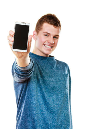 Communication and advertisement. Happy young man showing cell phone smartphone black blank screen isolated on white Foto de archivo