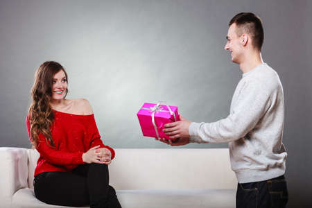 taking a wife: Couple and holiday concept. Handsome man surprising cheerful woman with gift box