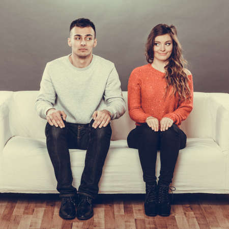 Shy woman and man sitting on sofa couch. First date. Attractive girl and handsome guy meeting dating and trying to talk.
