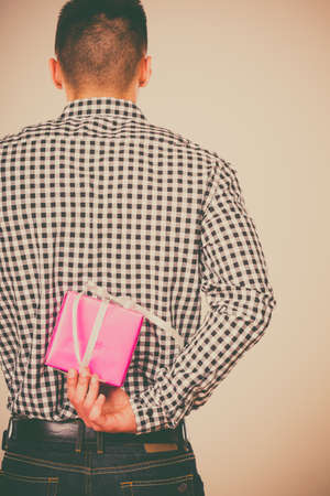 gift behind back: Man hiding pink gift box with white ribbon behind back. Male hand holding christmas present. Guy wearing flannel shirt. Birthday, holiday surprise.