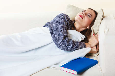 deprivation: Health balance sleep deprivation concept. Sleeping woman on sofa. Girl lying on couch with book relaxed or taking power nap after lunch.