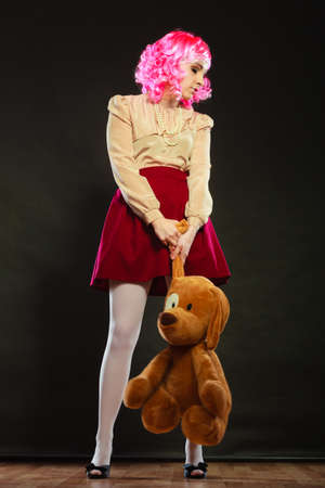 childlike: Mental disorder concept. Young childlike woman wearing like puppet doll and big dog toy standing dark black background