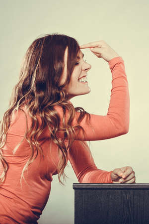 mocking: Woman gesturing with finger on her head. Are you crazy Girl mocking laughing at somebody.   Stock Photo