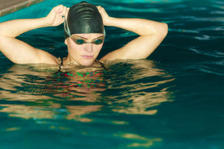 swim cap: Woman athlete in swimming pool water. Water sport comptetition exercise. Human swimmer training.