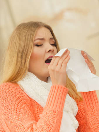 allergy: Sick woman in fall autumn park sneezing in tissue. Ill girl caught cold flu outdoor. Rhinitis or allergy. Health care. Stock Photo