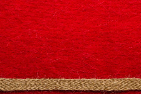 Border or frame formed by rough burlap rope over red textile background. Stock Photo