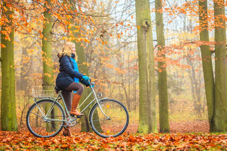 Happy active woman riding bike bicycle in fall autumn park. Glad young girl in jacket and scarf relaxing. Healthy lifestyle and recreation leisure activity.