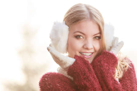 gorgeous: Portrait of pretty smiling fashionable woman in fall forest park. Happy gorgeous young girl in white earmuffs and sweater pullover. Autumn winter fashion.