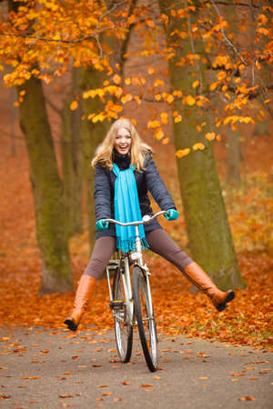 Fall active lifestyle concept. Beauty young woman girl waering vivid color shawl relaxing in autumnal park with bicycle outdoor