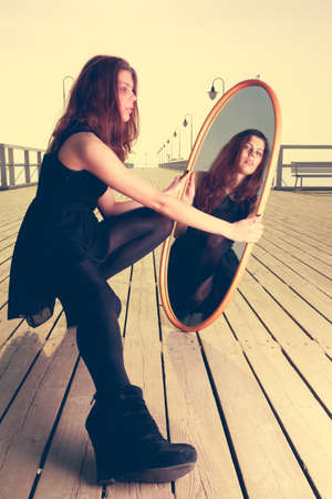 woman black: Solitude loneliness concept. Thoughtful young woman looks at the reflection in the mirror outdoors at sunset