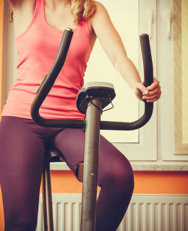 stationary bicycle: Active human working out on exercise bike stationary bicycle. Sporty person training at home. Fitness and weight loss concept.