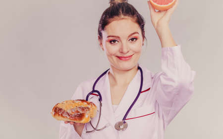 dietitian: Happy dietitian nutritionist with sweet roll bun and grapefruit. Woman holding fruit and cake comparing junk and healthy food. Right eating nutrition concept. Instagram filter. Stock Photo