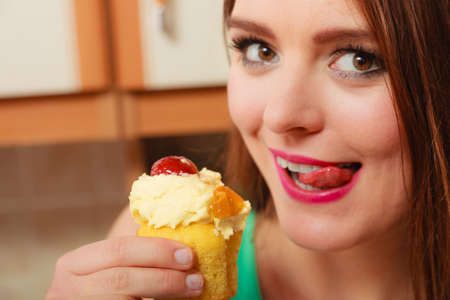 gluttony: Woman eating delicious cake with sweet cream and fruits on top licking her lips. Appetite and gluttony concept.