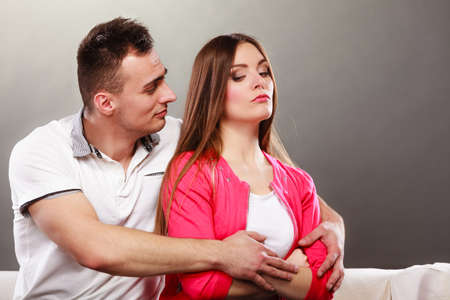conflict: Husband hugging unhappy wife. Offended angry woman girl not talking with man. Disagreement, conflict in a relationship. Stock Photo