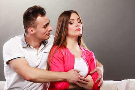conflict: Marido abrazando esposa infeliz. Ofendido niña mujer enojada sin hablar con el hombre. El desacuerdo, el conflicto en una relación.