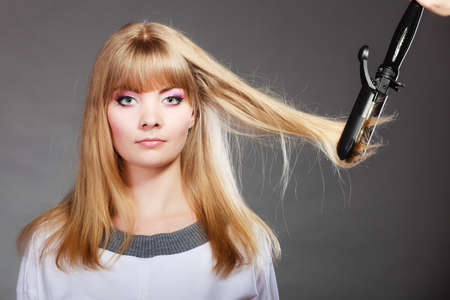 curling irons: Hairstyling. Attractive blonde woman long haired making hairstyle hairdo with electric hair iron straightener gray background