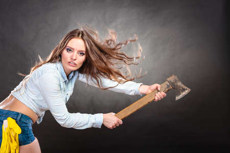 feministische: Sexy seductive woman holding axe chopper. Strong girl feminist working in man profession. Independent female. Studio shot. Stockfoto