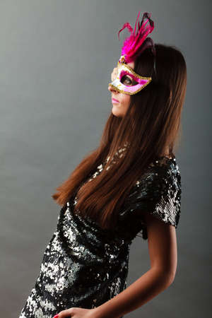 venetian mask: Holidays, people and celebration concept. woman with carnival venetian mask sequin evening dress on gray background.