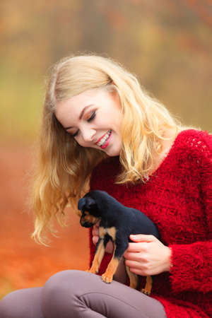 lovingly: Pets and people, pet adoption. Woman playing with her little dog pet outdoor, hugging lovingly embraces her puppy.