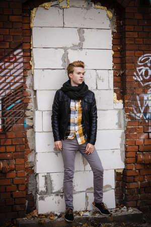 bel homme: Longueur de beau mode homme ext�rieur � l'�tablissement de la ville, mod�le masculin portant la veste foulard noir et chemise � carreaux contre le mur de briques Banque d'images