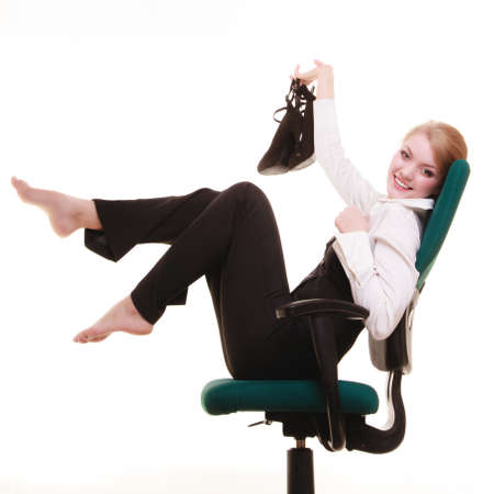 break from work: Break from work. Young businesswoman happy girl with shoes in hand relaxing on chair isolated on white. Business. Stock Photo