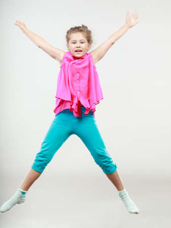 Excited happy little girl jumping for joy in air. Joyful cheerful kid in studio with arms raised up.