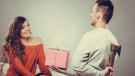 intention: Sneaky insincere man holding axe giving gift present box to woman. Husband concealing hiding his true feelings from happy trusting wife. Untrue false intention. Relationship problems.