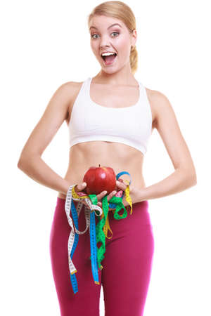 measures: Happy joyful young woman girl holding apple and tape measures. Slimming and dieting. Healthy lifestyle nutrition concept. Isolated on white.