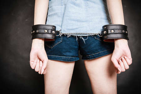 manacles: Arrest and jail. Closeup of leather handcuffs on hands of criminal woman prisoner girl on gray. Punishment.