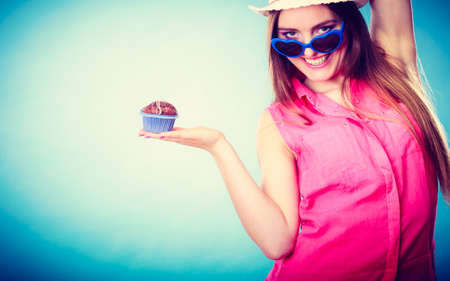 sweet food happiness and people concept. Smiling summer fashionable woman wearing straw hat heart shaped sunglasses holds cake cupcake in hand blue background Stock Photo
