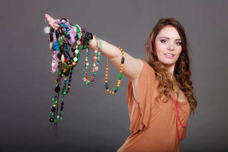 plentiful: Pretty young woman wearing bracelets and rings holding many plentiful of precious jewelry necklaces beads. Gorgeous fashion girl. Stock Photo