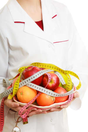 dietitian: Closeup woman in white lab coat holding fruits and colorful measure tapes isolated. Doctor dietitian recommending healthy food. Dieting