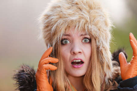 gorgeous woman: Portrait of scared afraid pretty woman talking on mobile phone. Gorgeous young girl in fur winter hat and jacket. Autumn fashion and communication.