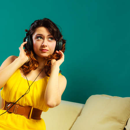 people listening: Young people leisure relax concept. Closeup teen cute girl in big headphones listening music mp3 relaxing on green blue background Stock Photo