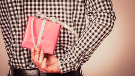in behind: Man hiding pink gift box with white ribbon behind back. Closeup of male hand holding christmas present. Guy wearing flannel shirt. Birthday, holiday surprise.