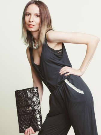 style: Donna alla moda elegante con borsa in pelle. Ragazza alla moda in possesso di borsa nera. Le donne della moda Vogue. Studio.