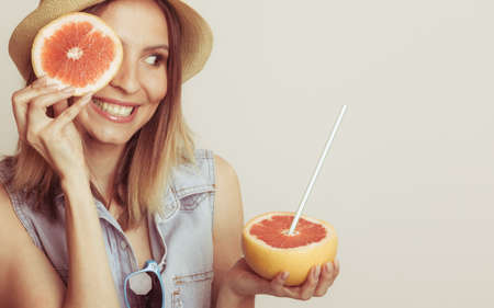 grapefruit: Woman having fun covering her eye with grapefruit. Happy summer vacation holiday. Healthy food.