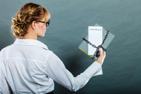 roped: Business concept, limited by contract. Woman holding in hands paper document chained with padlock