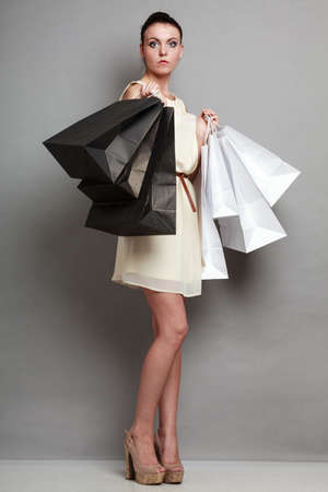 shopaholism: Woman in full length sale and retail concept. Elegant girl with black and white shopping bags in hands on grey background studio shot. Stock Photo