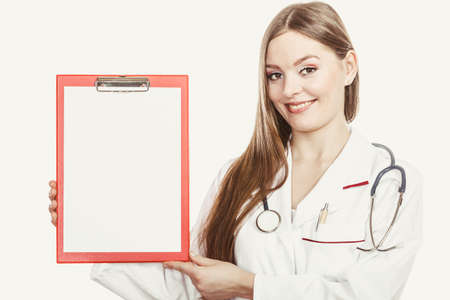 commercial medicine: Woman medical doctor with stethoscope, clipboard and pen wearing white coat isolated. Professional health care advertisement.