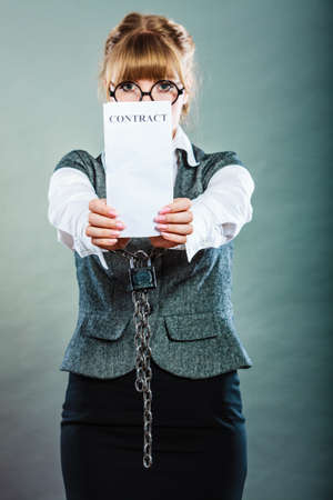 chained: Business concept. Serious businesswoman with chained hands holding contract Stock Photo