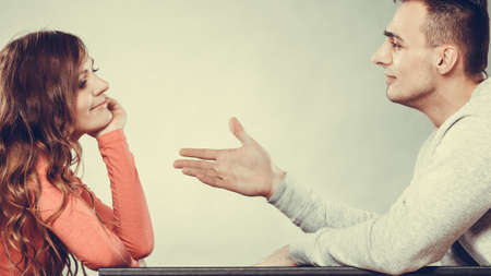 argument from love: Man trying to reconcile with woman. Couple making up after quarrel. Husband reaching out to wife.